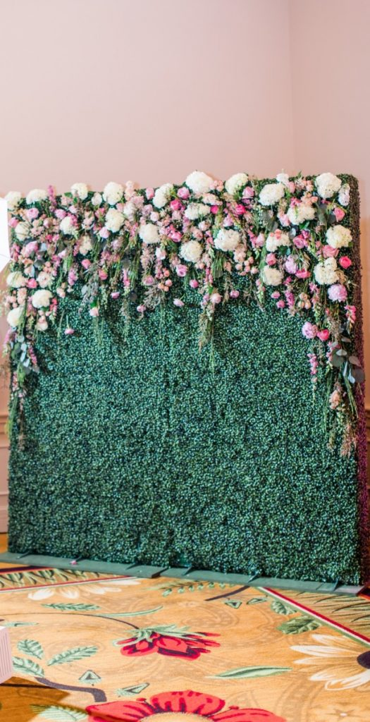 Hedge Wall Used as Photo Backdrop with Floral Attached by Florist
